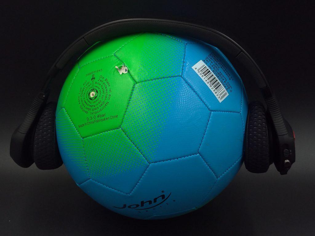 Kopfhörer auf Fußball gespannt